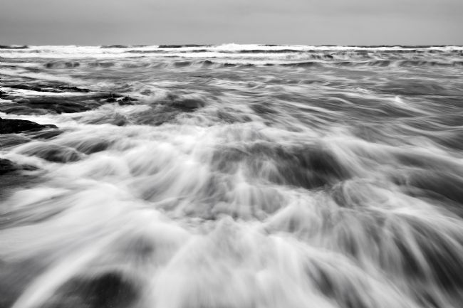 Kevin Pawsey | Soft waves over the rocks in black and white