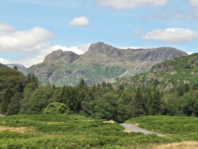yvonne carroll | Remote road to Langdale in the Lake District with the Langdale Pike mountains towering above the road